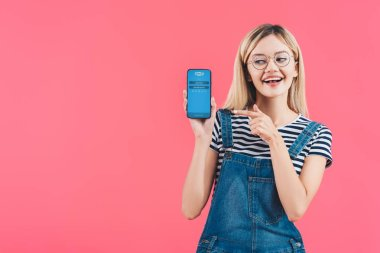 Portrait of smiling woman in eyeglasses pointing at smartphone with skype logo isolated on pink stock vector
