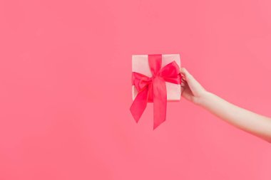 cropped shot of woman holding gift isolated on pink
