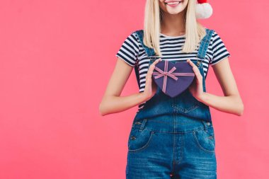 cropped shot of woman in santa claus hat with heart shaped gift isolated on pink