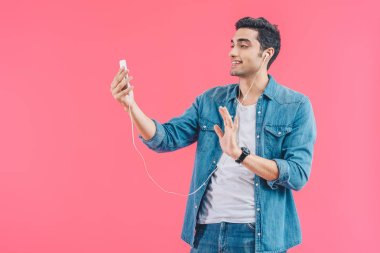 portrait of young man in earphones waving to smartphone isolated on pink