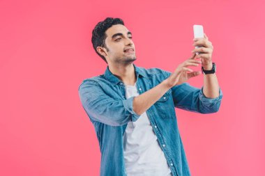 Portrait of young man taking selfie on smartphone isolated on pink stock vector