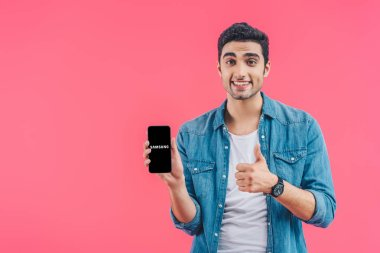 Cheerful young man doing thumb up gesture and showing samsung smartphone isolated on pink stock vector