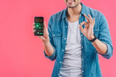 partial view of young man doing ok sign and showing smartphone with marketing analysis  isolated on pink