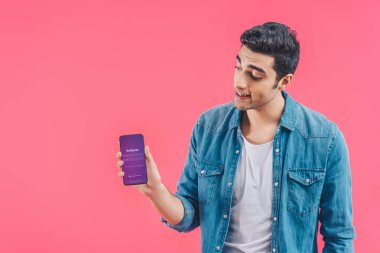 young man showing smartphone with instagram website isolated on pink