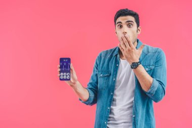 shocked young man covering mouth by hand and showing smartphone with medical application isolated on pink