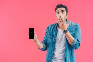 shocked young man covering mouth by hand and showing samsung smartphoneisolated on pink