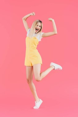 excited young woman jumping with raised arms isolated on pink
