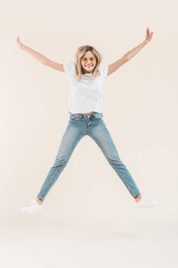 Happy young woman in eyeglasses jumping with raised arms isolated on beige stock vector