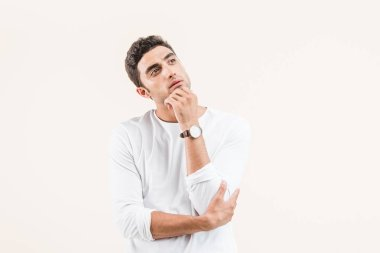 thoughtful young man with hand on chin looking away isolated on beige