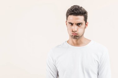 angry young man blowing cheeks and looking at camera isolated on beige
