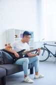 Fotografie handsome asian man playing F major chord on unplugged electric guitar at home