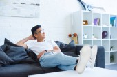 smiling handsome asian man sitting on sofa with legs on table at home, looking away