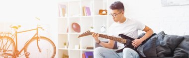 panoramic view of handsome left-handed asian man playing electric guitar on sofa at home