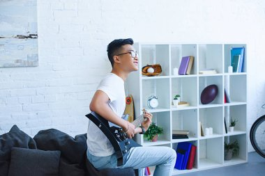 side view of smiling handsome asian man playing unplugged electric guitar at home