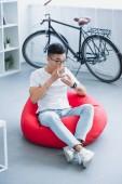 magas szög kilátás szép ázsiai ember ül a bab zsák széket, és ivott tea otthon