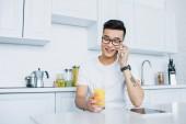 Fotografie Lächelnder junger asiatischer Mann mit Brille hält ein Glas Saft in der Hand und spricht mit dem Smartphone, während er in der Küche sitzt