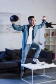 Fotografie asiatische junge Rugby-Ball halten und beobachten Sport zu Hause passen triumphiert