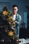 Fotografie young asian man in eyeglasses decorating christmas tree at home