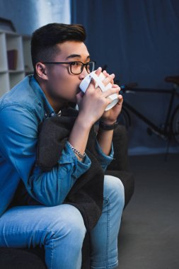 handsome young asian man in spectacles sitting on sofa and drinking from mug