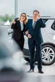Fotografie businessman and businesswoman choosing new automobile in showroom