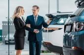 Fotografie Unternehmer und Unternehmerin Wahl neues Automobil im showroom