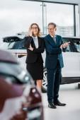 Fotografie businessman talking on smartphone while businessman choosing new automobile in showroom
