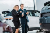 Fotografie businessman and businesswoman with smartphone choosing new automobile in showroom
