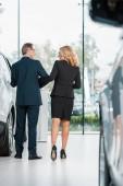 zadní pohled na podnikatele chůzi v autorizovaném salonu při výběru nového vozu