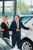 businesspeople walking in dealership salon while choosing new car