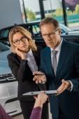Fotografie zmatený podnikatelé poslechu ženské auto prodejce s doklady v showroomu