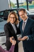 částečný pohled ženské auto dealer dává klíč od auta k usmívající se pár podnikání v oblasti formálního oblečení v autorizovaném salonu
