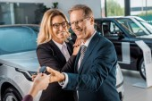 partial view of female car dealer giving car key to smiling business couple in formal wear in dealership salon