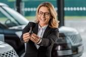Happy podnikatelka v oblasti formální oblečení drží klíče od nového vozu v autorizovaném salonu