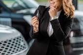 Oříznout záběr usměvavá podnikatelka drží klíče od auta na showroomu