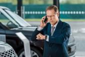komoly felnőtt üzletember autó kereskedések szalonban telefonon beszélt, és nézte karóra