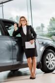 usmívající se žena auto prodejce s tabletem, opíraje se o auto v showroomu a při pohledu na fotoaparát