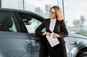 Fotografie Krásné ženské auto prodejce s tabletem, opíraje se o auto v showroomu
