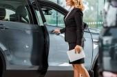 Oříznout záběr ženské auto prodejce s tabletem, otevírání aut v showroomu