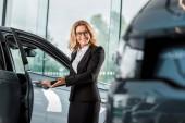 atraktivní usměvavá žena auto prodejce otevírání auto v showroomu