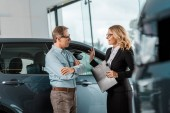 Photo handsome adult man and female car dealer chatting at showroom