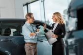 dospělý muž a žena auto dealer chatování na showroomu