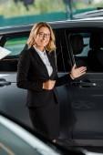 Fotografia concessionario di auto femmina bella che punta alle auto in showroom