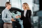 dospělý muž vezme klíč od auta od ženské auto prodejce na showroomu