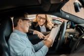 dospělý muž podepsání smlouvy s ženské autoprodejce zatímco sedí v autě