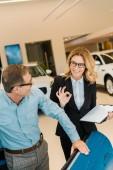 Fotografie Erwachsener Mann überprüft Luxus-Sportwagen mit Autohändlerin im Showroom, während sie Okay-Zeichen zeigt