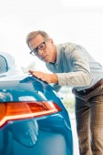 Fotografie handsome adult man touching luxury sport car at showroom