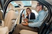 boční pohled šťastné dospělé muže a ženy autoprodejce sedí na zadním sedadle luxusní auta a mluví