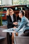 Fotografie Erwachsene Kunden und weibliche Autohändler Händeschütteln im showroom