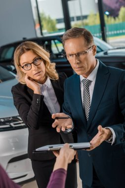 confused businesspeople listening to female car dealer with papers in showroom
