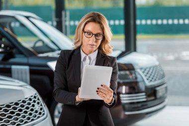 beautiful female car dealer using tablet at showroom